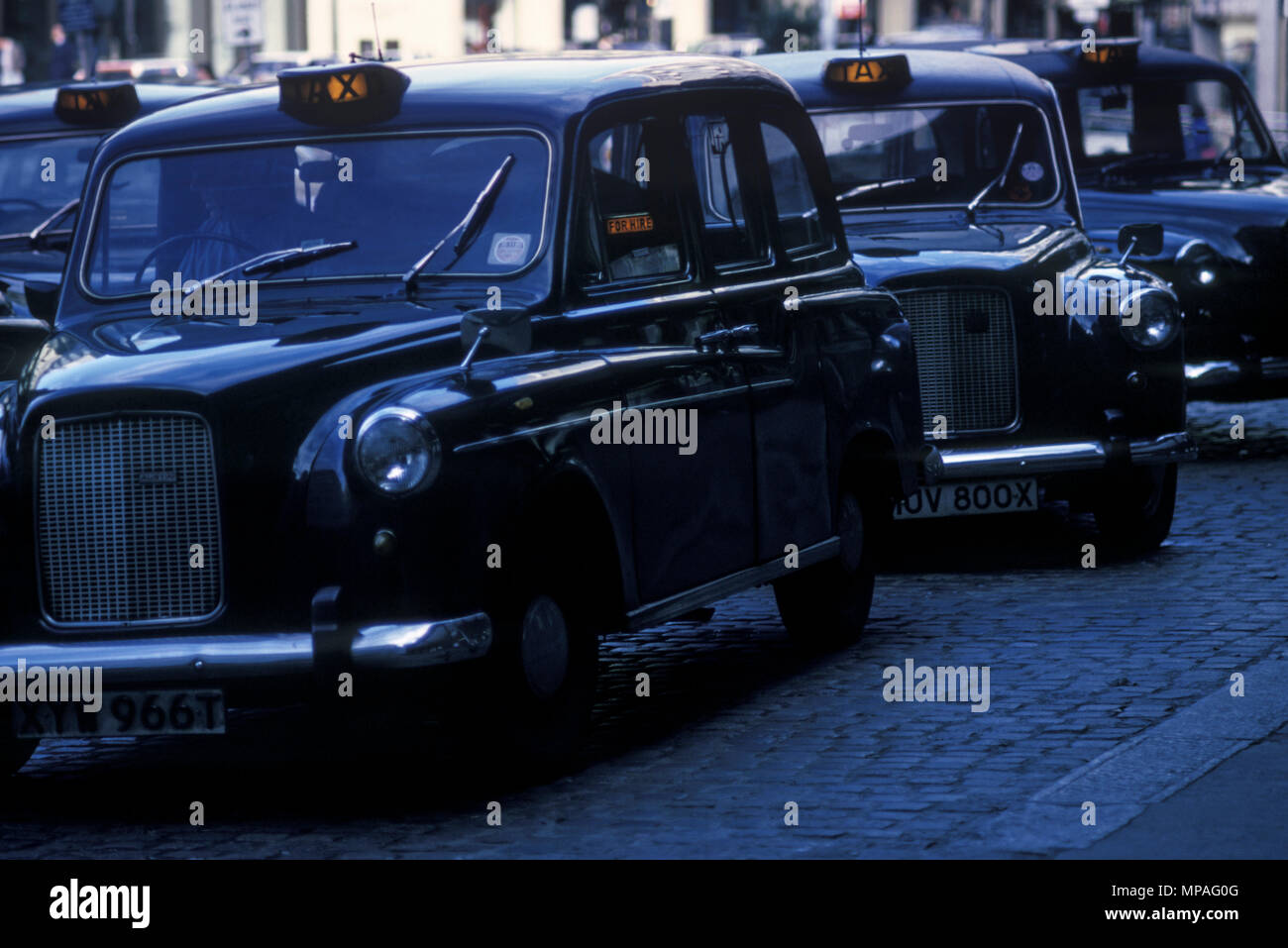1988 HISTORICAL LINE OF BLACK TAXI CABS FOR HIRE VICTORIA STATION TAXI RANK LONDON ENGLAND UK Stock Photo