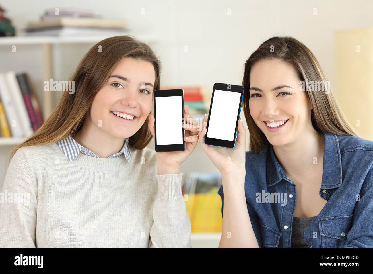 Front view portrait of two happy students showing to camera smart phone screens mockup - Stock Image