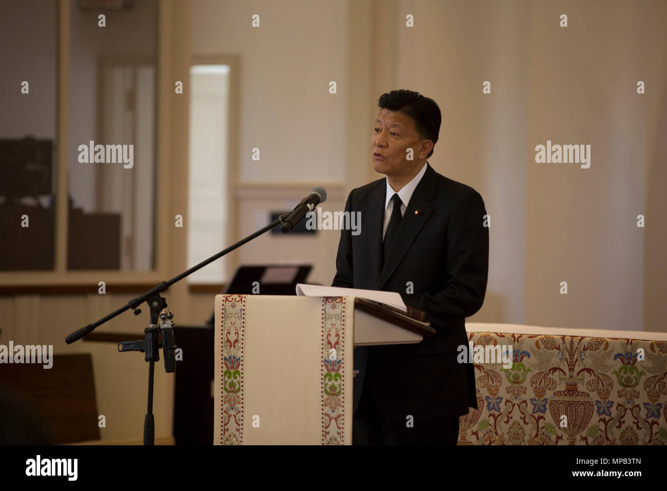 """Yoshitaka Shindo, member of the National Diet of Japan gives remarks during the Memorial Service of retired U.S. Marine Corps Lt. Gen. Lawrence F. Snowden at the U.S. Marine Memorial Chapel, Quantico, Va., April 8, 2017Snowden retired in 1979 after nearly 40 years of service, fought in engagements during World War II, the Korean War, and Vietnam. He passed away Feb. 18, 2017. He was prominently known after retirement for organizing joint """"Reunion of Honor"""" missions which is an opportunity for Japanese and U.S. veterans and their families, dignitaries, leaders and service members from both nati Stock Photo"""