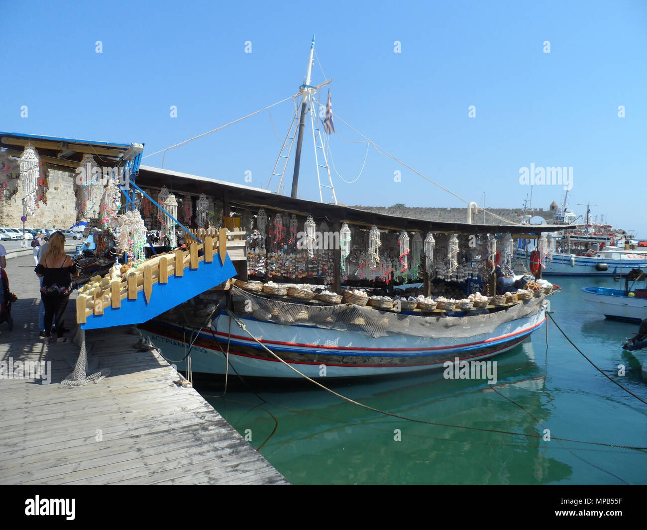 Tourists peruse the wares on a Greek fishing boat transformed into a souvenir shop at Rhodes harbour, greece. - Stock Image