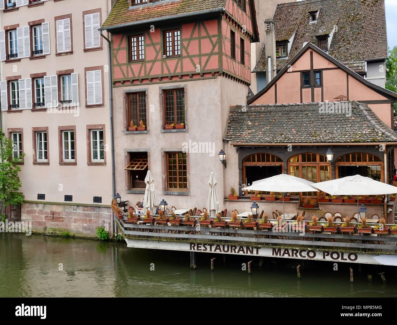 People eating on the terrace of a pizza restaurant on the edge of the Ill River, Strasbourg, France - Stock Image