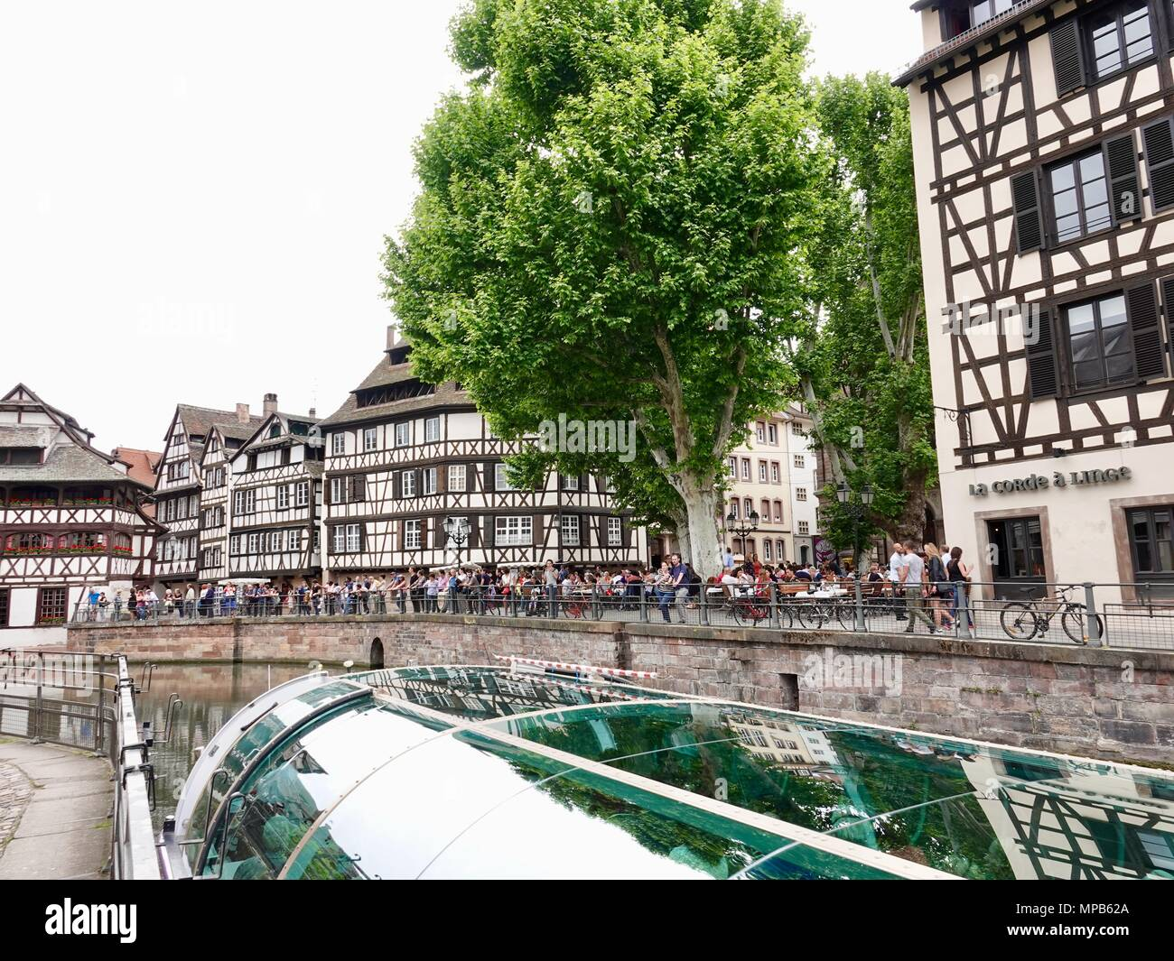 People lined up along the canal to watch as tourist boat exits a lock. Strasbourg, France - Stock Image