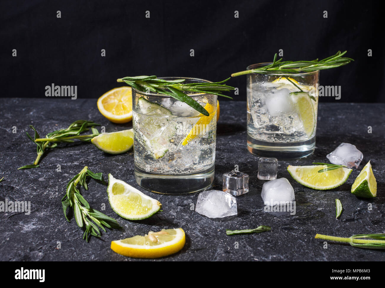 Alcoholic drink gin tonic cocktail with lemon, rosemary and ice on stone table. Stock Photo