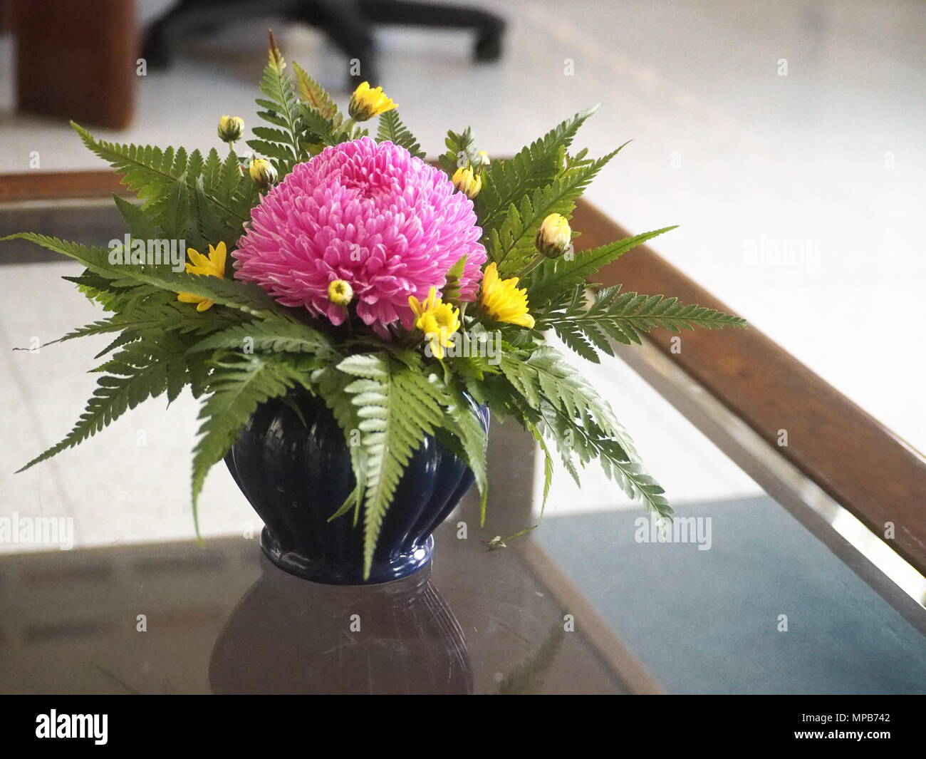 Tabletop Flower Arrangement On A Glass Coffee Table In An Office Waiting Area Stock Photo Alamy