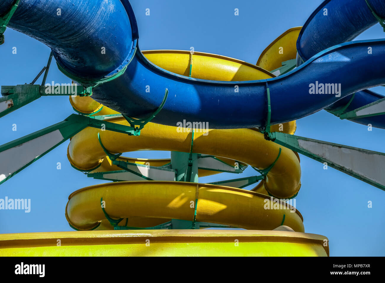 Summer fun, aquapark. Modern water slide park, yellow and blue slides. Sunny day, clear blue sky cloudless, close up, seen from below, pov. - Stock Image