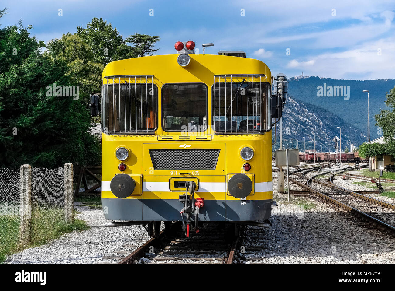 Railway construction machinery, yellow catenary maintenance draisine standing on an open track, just outside Nova Gorica railway station, Slovenia, EU Stock Photo