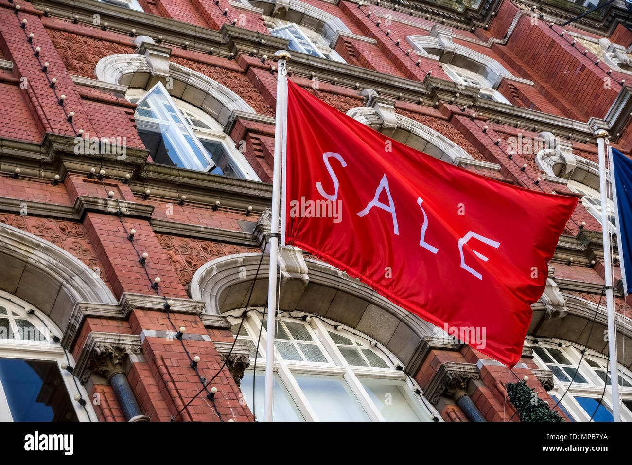 Shopping, sale red flag flying at Arnotts Department Store, brownstone building façade, on Henry Street. Dublin, Ireland. Close up, low angle view. - Stock Image