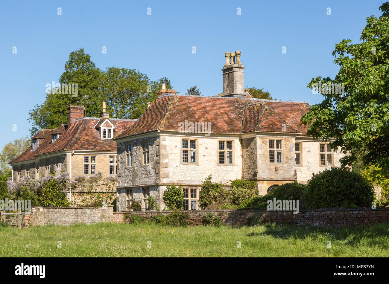 Large detached extended historic farmhouse built from chalk stone in village of Compton Bassett, Wiltshire, England, UK - Stock Image