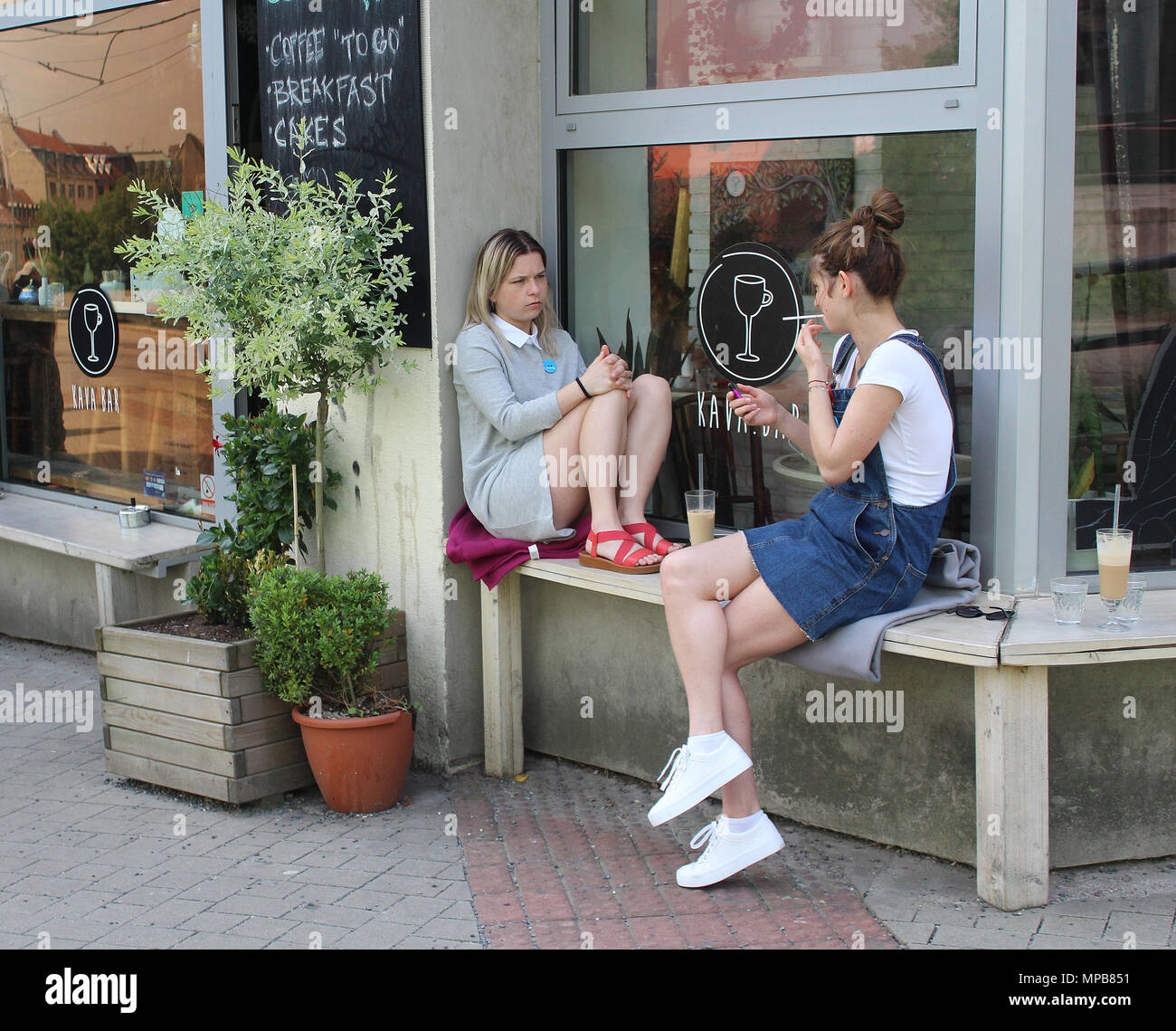 City life - two young girls sitting in front of a cafeterie in the street of Bratislava, capital of Slovakia and chatting - Stock Image