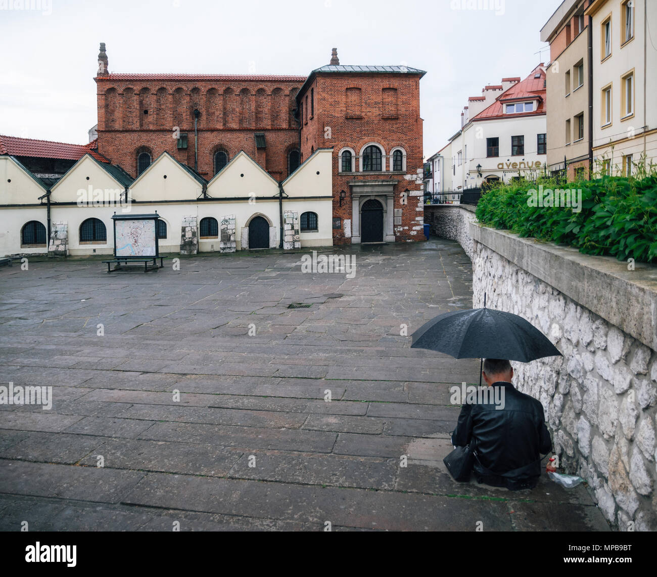 Krakow, Poland - May 23, 2017: Adult man sits with umbrella against old Synagogue in the historic Kazimierz, old jewish district in Krakow, Poland - Stock Image