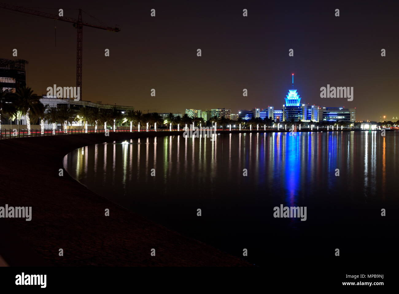 Dubai, United Arab Emirates - May 21, 2018: Dubai Silicon Oasis Headquarters Building with Lake view at night, Established in 2014 a free zone owned b - Stock Image