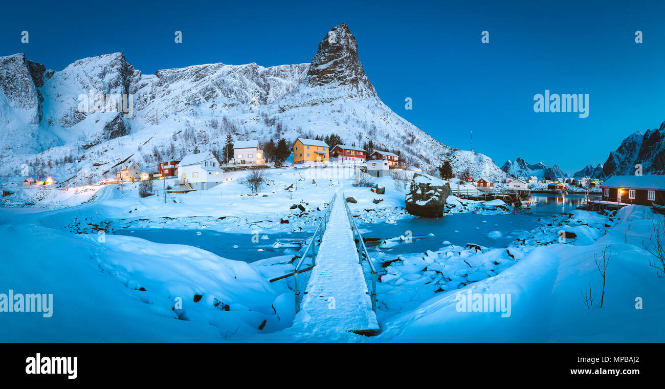 Famous fishing village of Reine with a small bridge in magical morning twilight at dawn in winter, village of Reine, Lofoten Islands, Norway - Stock Image