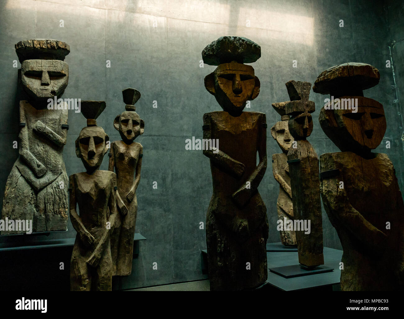 Exhibit in Museum of Pre-Columbian Art, Santiago, Chile. Wooden figures with top knots, called Chemamulles, found at Andean culture Mapuche cemeteries - Stock Image