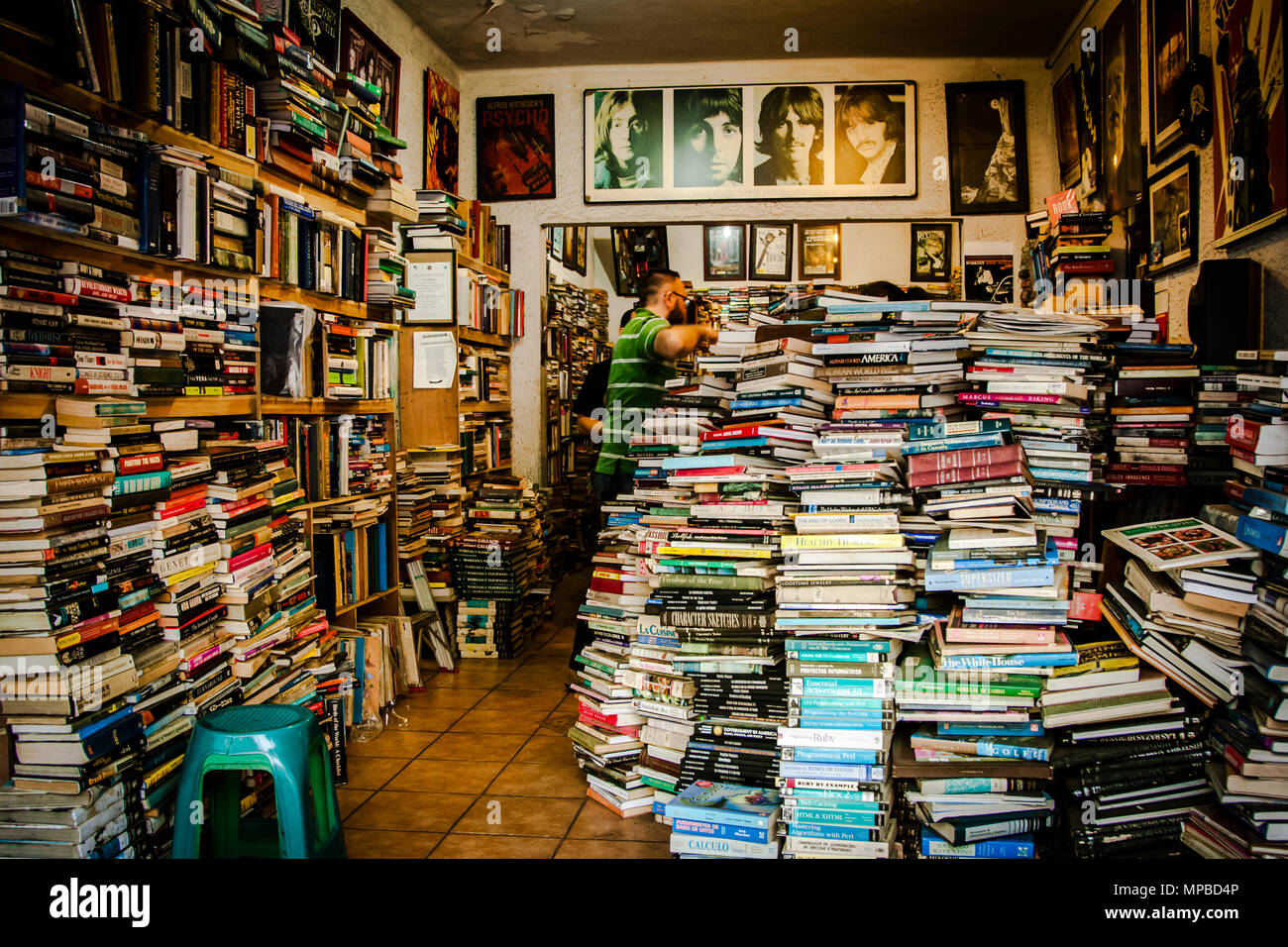 Book shop in San Jose, Costa Rica with piles of books stuffed on shelves and on the ground. In the backround you see  portraits of the Beatles. - Stock Image