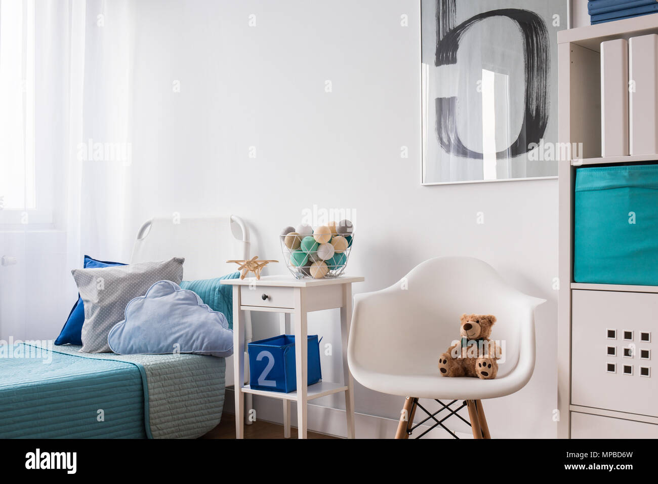 Seaside decorations on nightstand near blue single bed in ...