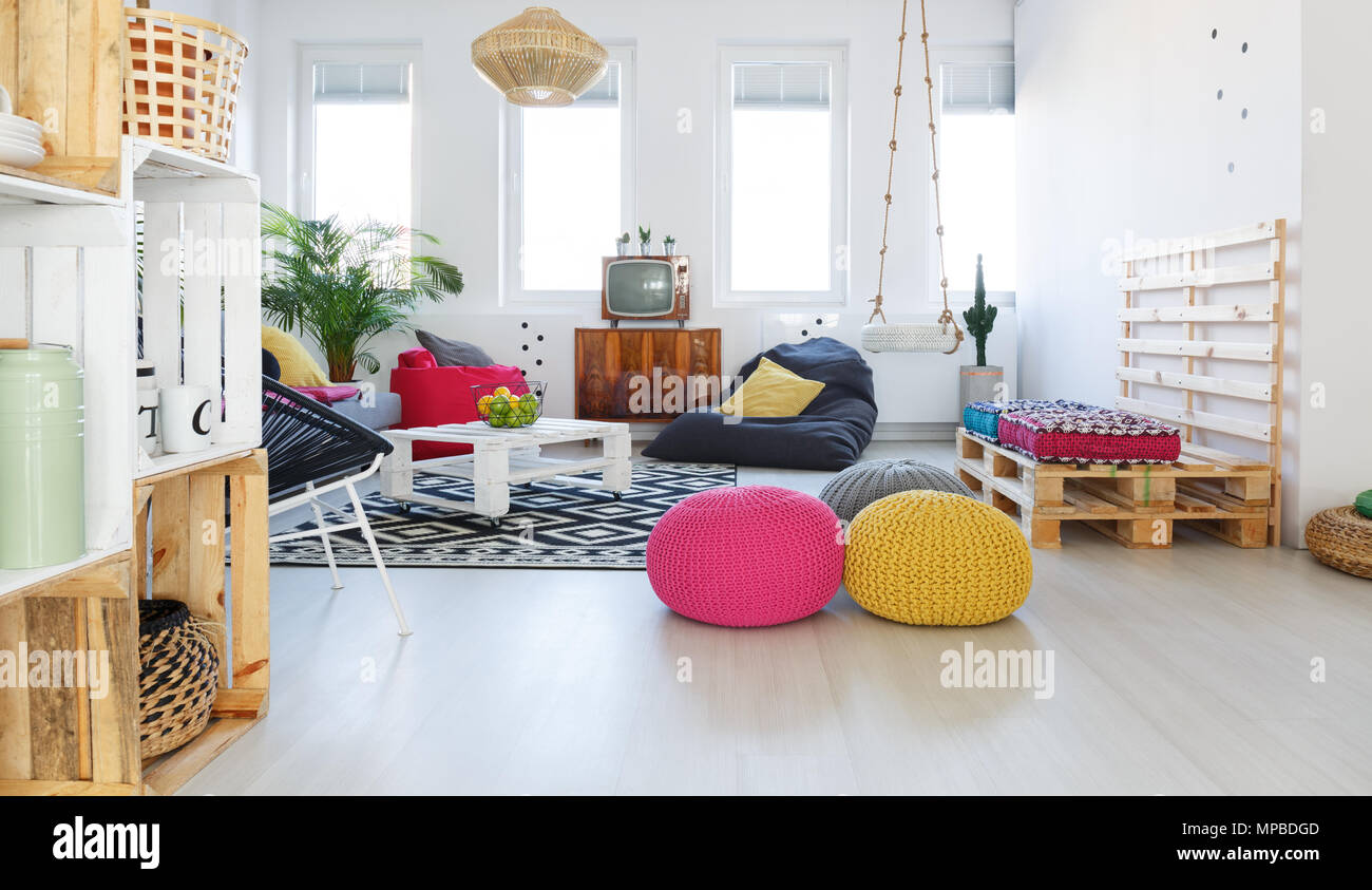 Colorful retro living room with pouf, tv, swing, crate furniture ...