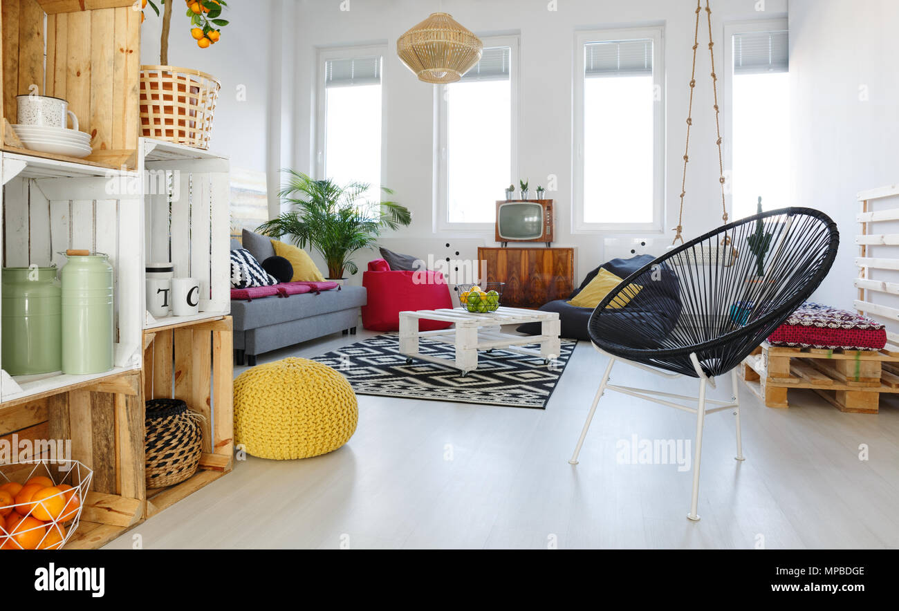 Living room with round chair, yellow pouf, sofa, pallet furniture ...