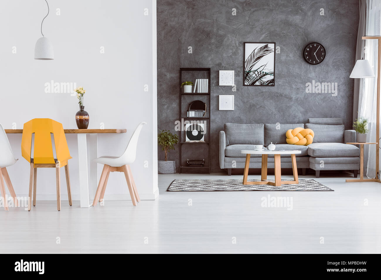 Decorative Vase On Dining Table With Yellow Chair In Living Room With Grey  Settee Against Dark Wall