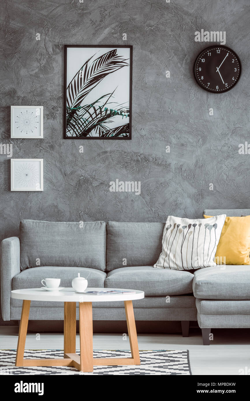 Simple Living Room With Posters And Black Clock On Concrete