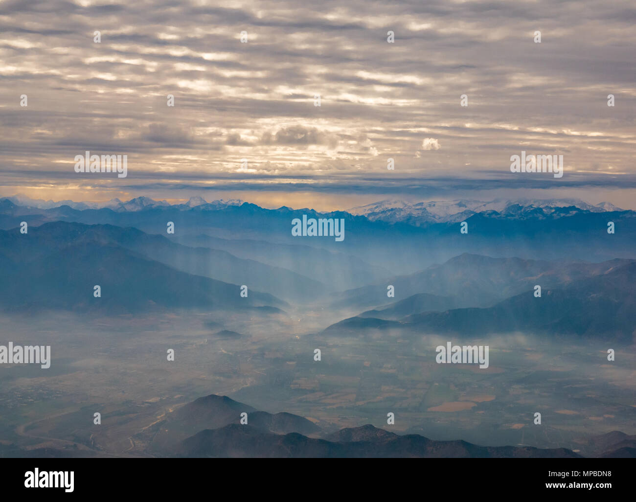 View from plane window flying South from Santiago, Chile with Andes mountain peaks and cloud layers broken by shafts of light falling on valley Stock Photo