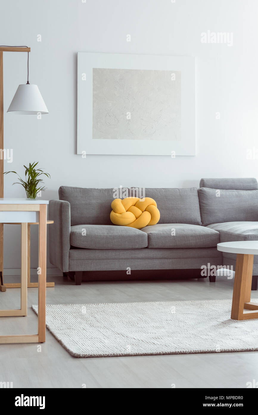 Yellow Knot Pillow On Grey Sofa In Cozy Living Room With White
