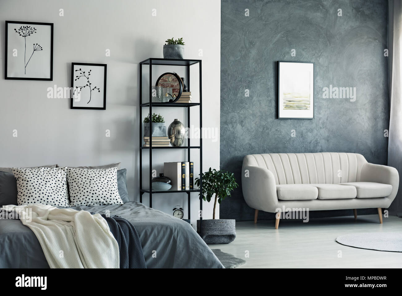 Beige sofa against concrete wall with painting in bedroom ...