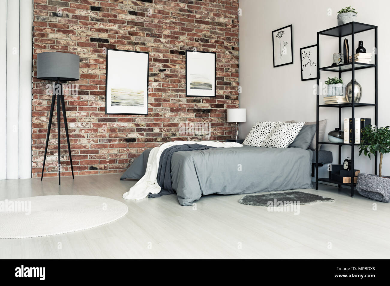 Lamp and white carpet in grey bedroom with bright pillows on bed and ...
