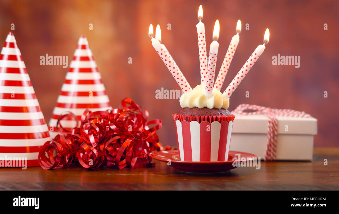 Birthday Cupcake With Candles And Gift Against A Rustic Wood Background