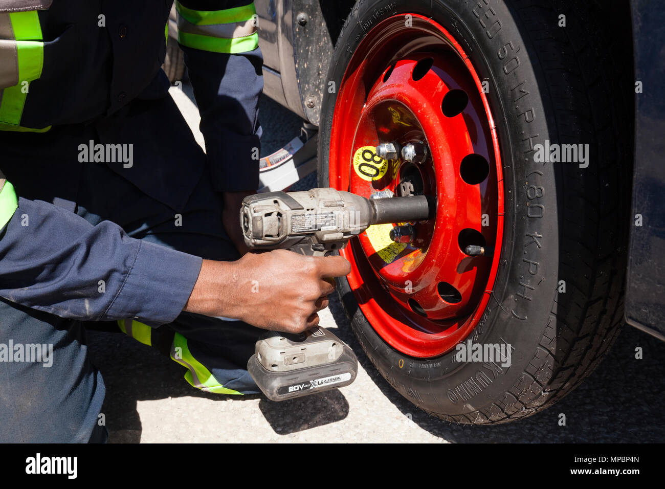 A service technician or person installing a spare tire or tyre using an impact wrench. - Stock Image