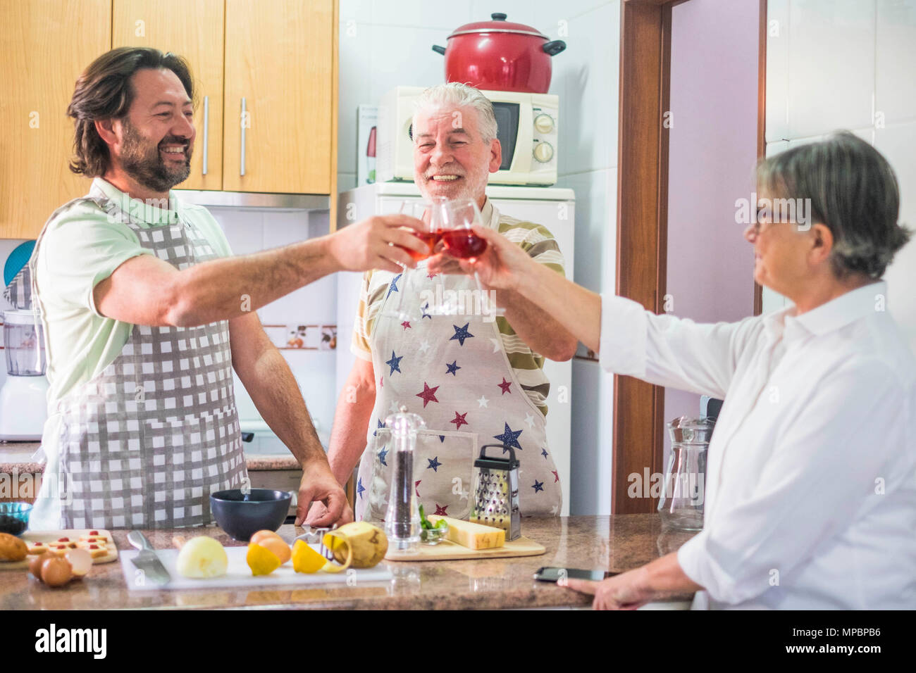 3-person family toasting with red wine while preparing dishes prepared in the home kitchen - Stock Image