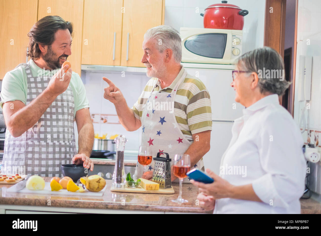 Indoor kitchen scene tiwh a family cooking. Father, mother and son. Senior couple and middle aged male. Joking and telling daily concept. - Stock Image