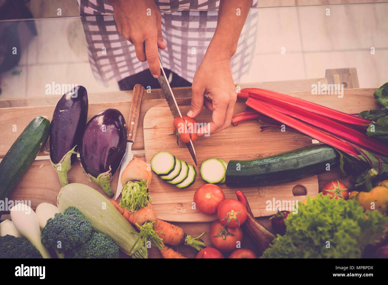 Closeup of Human hands cooking food, vegetables salad in kitchen. Preparing fresh meal in the kitchen. Healhty lifestyle concept at home eating raw in - Stock Image