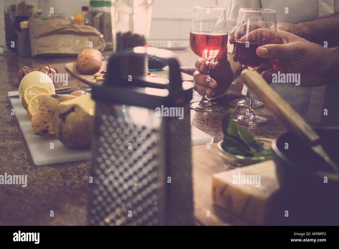 vintage filter for a cocktail home scene with three hands from two men and a woman at home. Domestic scene of usual life for a nice time together. - Stock Image