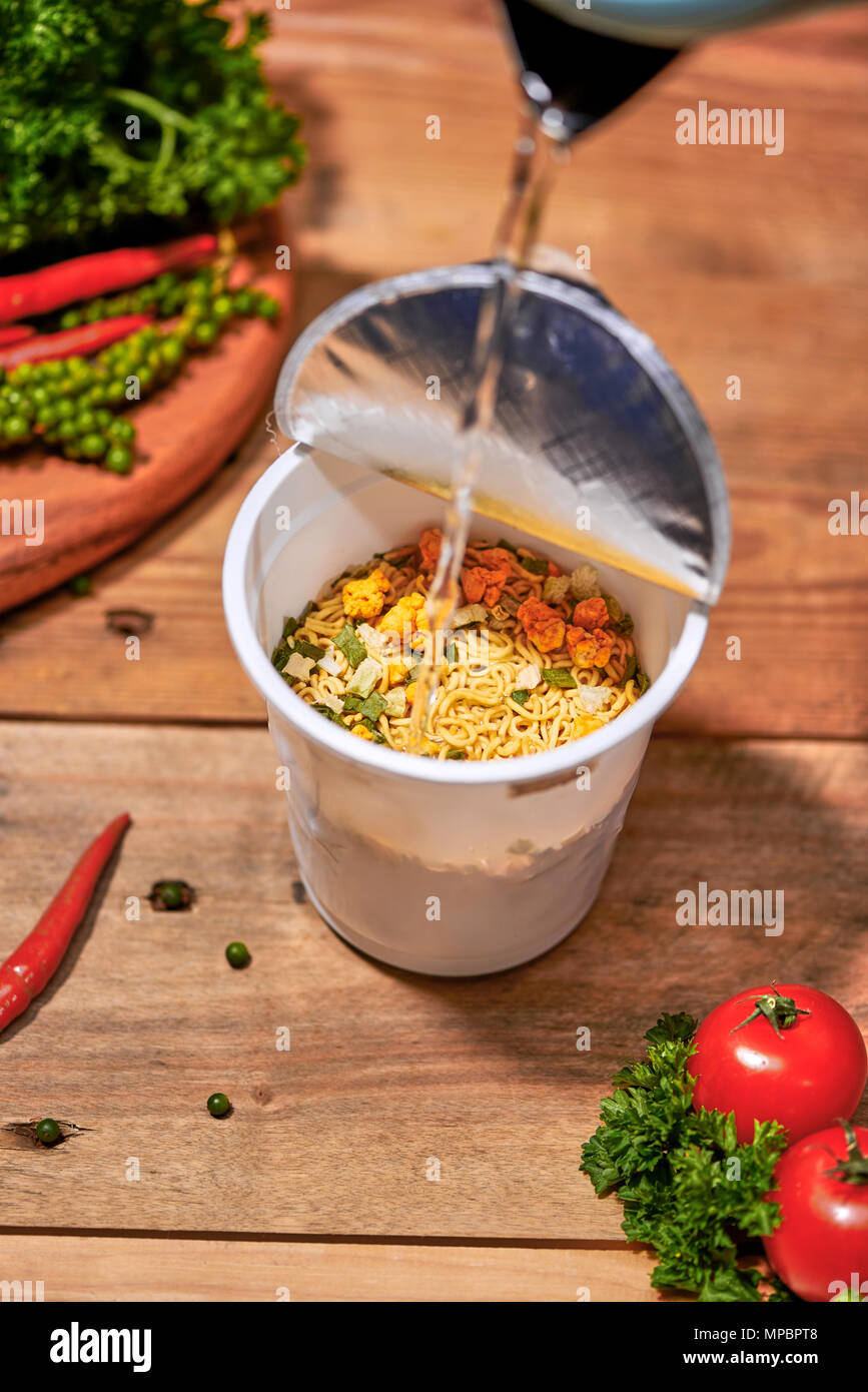 instant noodle, asian fast food, noodle cup on wooden background. - Stock Image