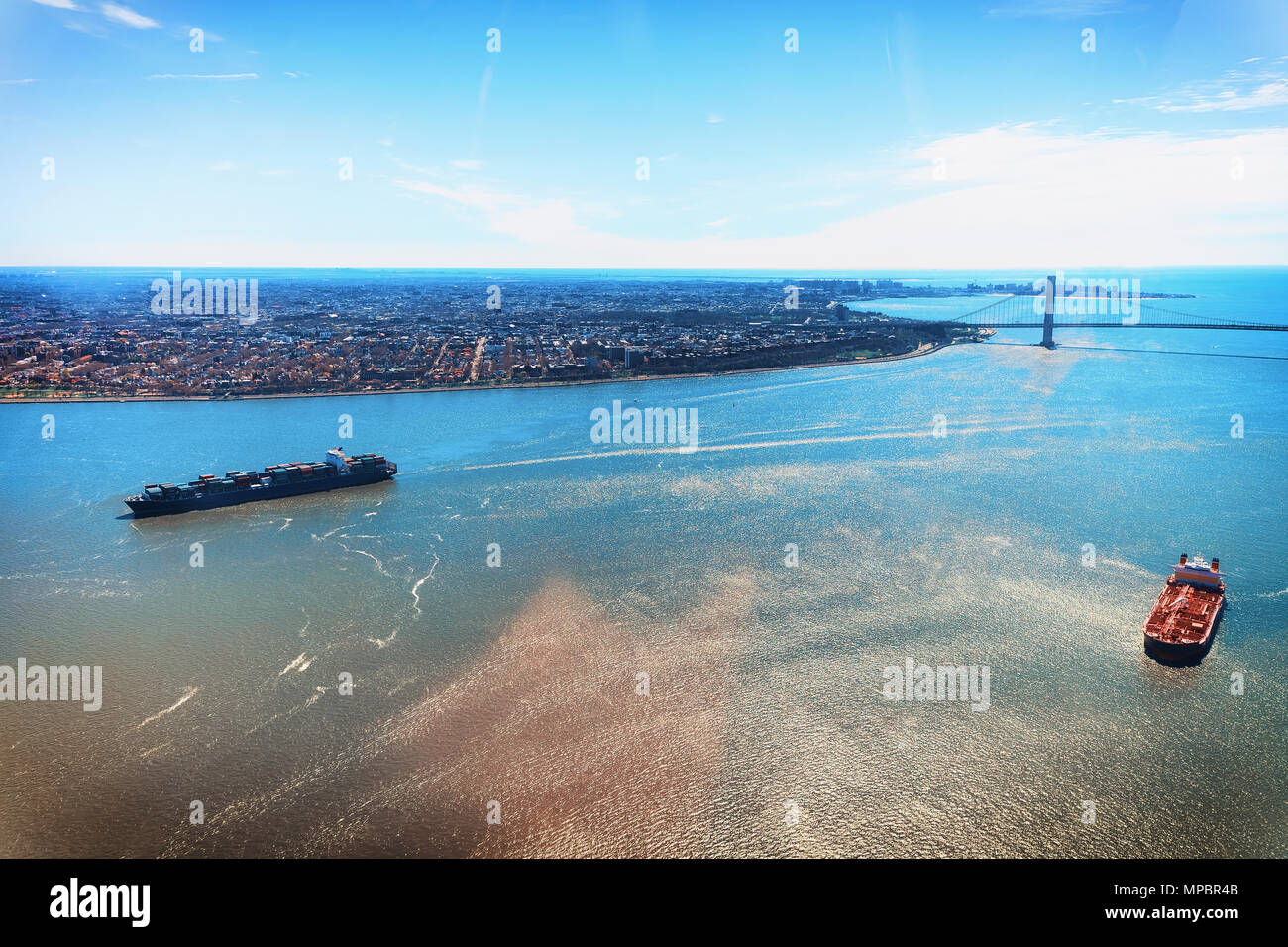 Aerial view on Containers Vessel and Manhattan Bridge structure with New York skyline in the morning over east Hudson River, New York City, USA Stock Photo