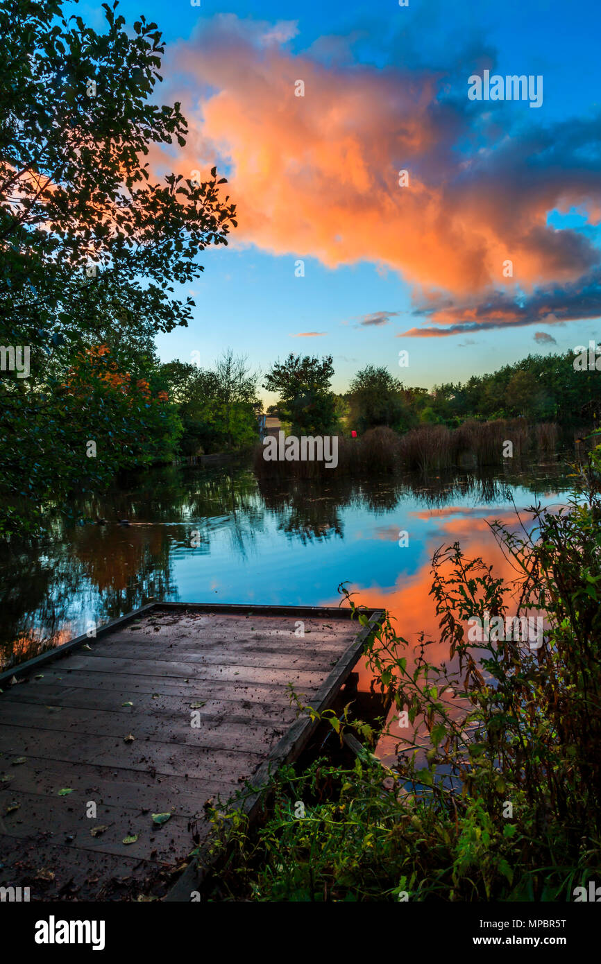 The sunset over a fishing peg an a lake in Baggeridge Country Park. - Stock Image