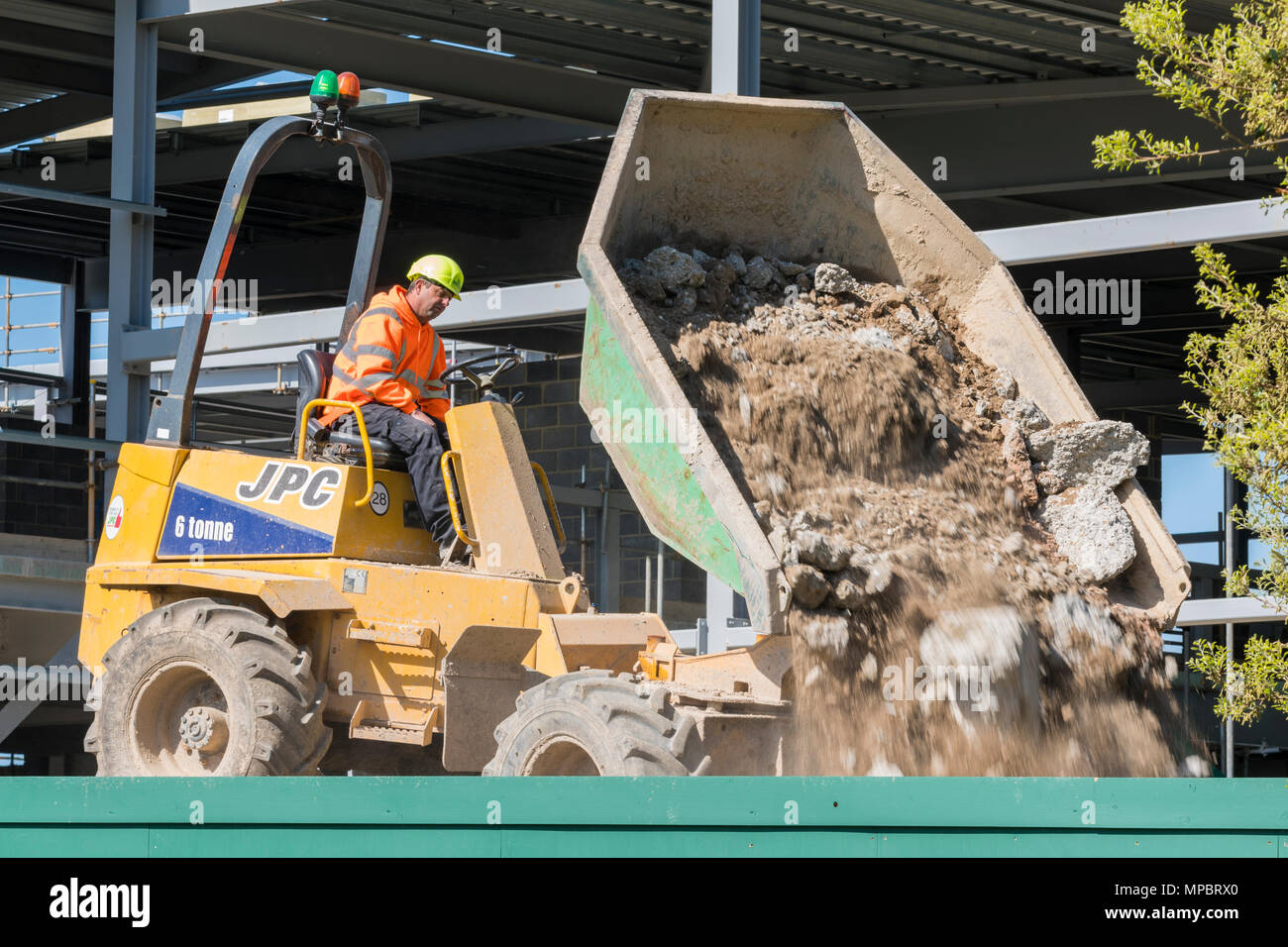 Construction vehicle on a building site tipping out rubble. JPC vehicle. - Stock Image