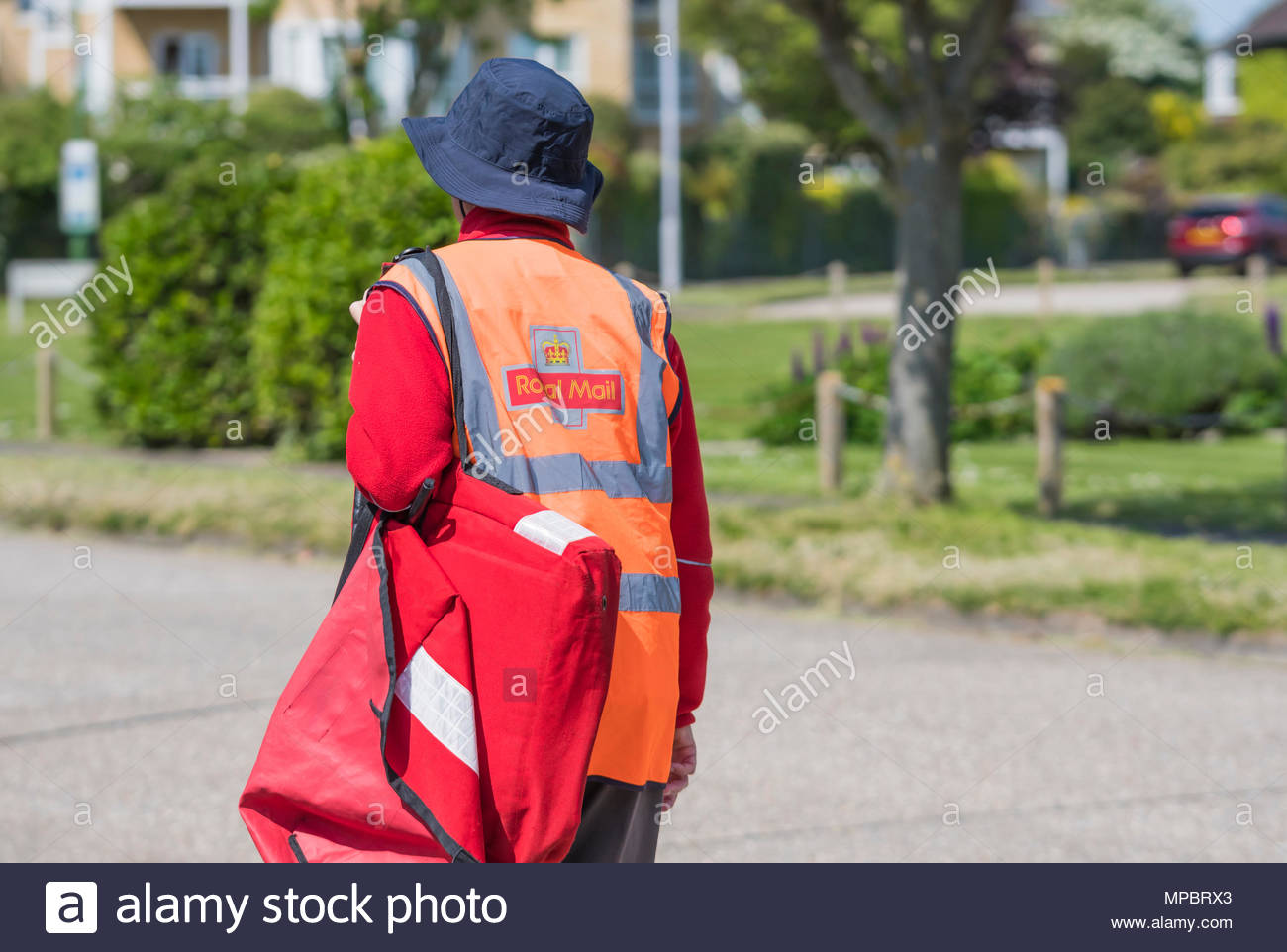 British Royal Mail Postman walking in a residential area carrying a red satchel of letters, for morning deliveries in West Sussex, England, UK. - Stock Image