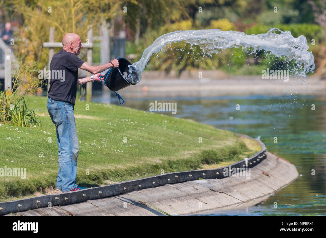 Man throwing treated water into a lake in a park after mixing water with chemicals. Lake maintenance in the UK. Maintaining water in a lake. - Stock Image