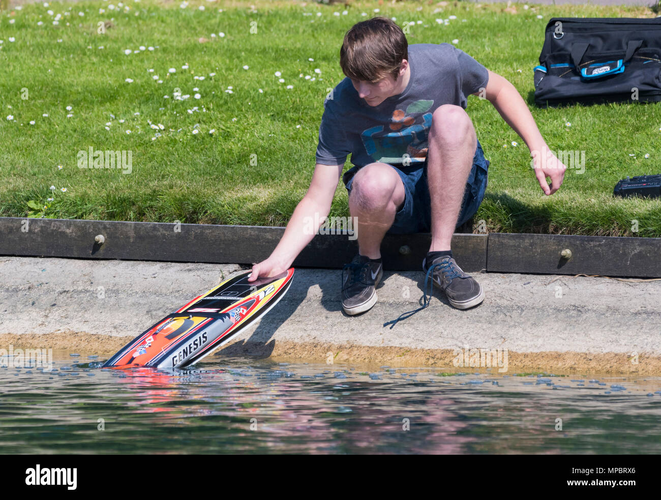 Young man taking a model radio controlled boat out of the water. Remote controlled speedboat. - Stock Image