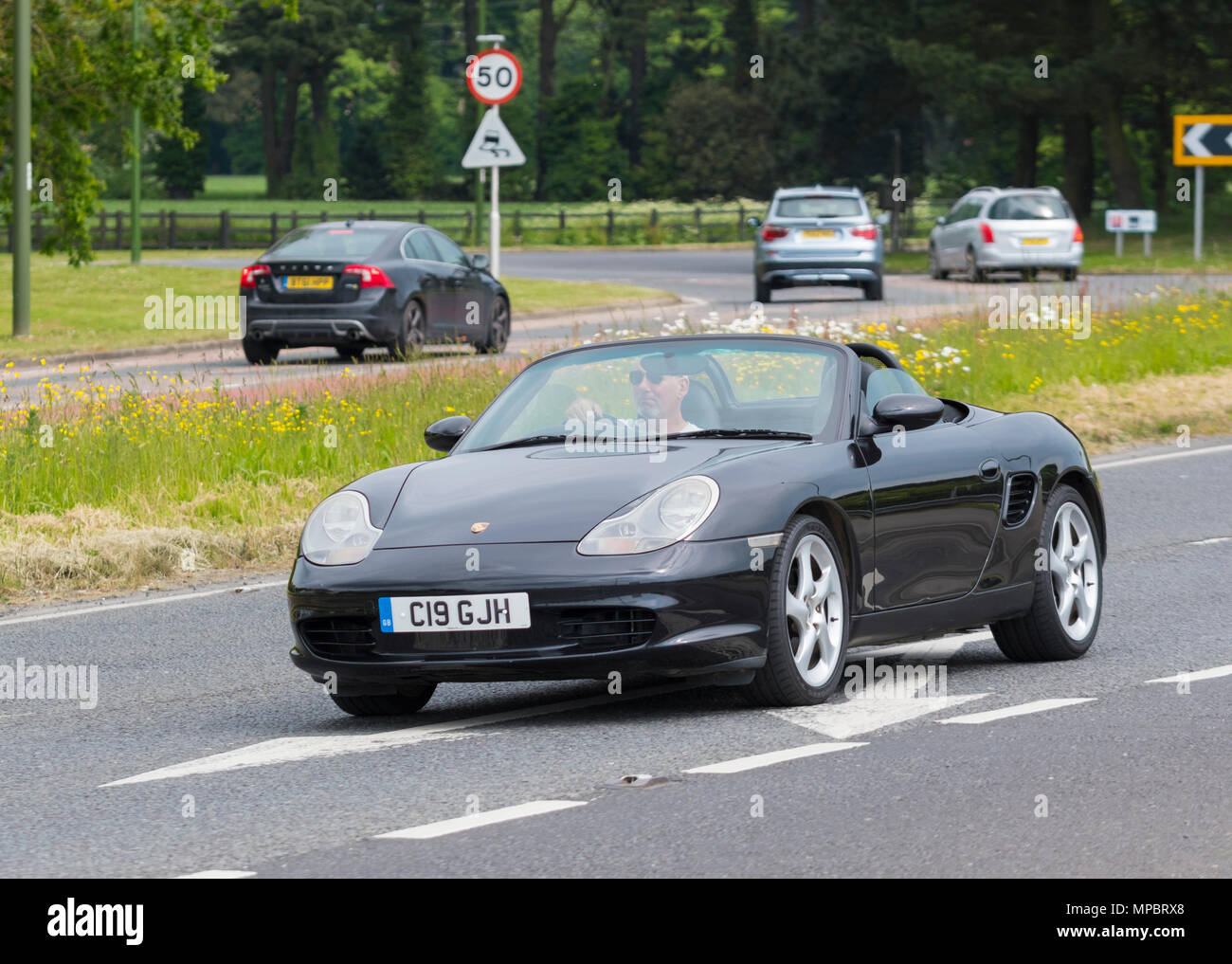 Black Porsche Boxter convertible sports car with the top down on a hot day in the UK. Porsche Boxter 2004 model. - Stock Image