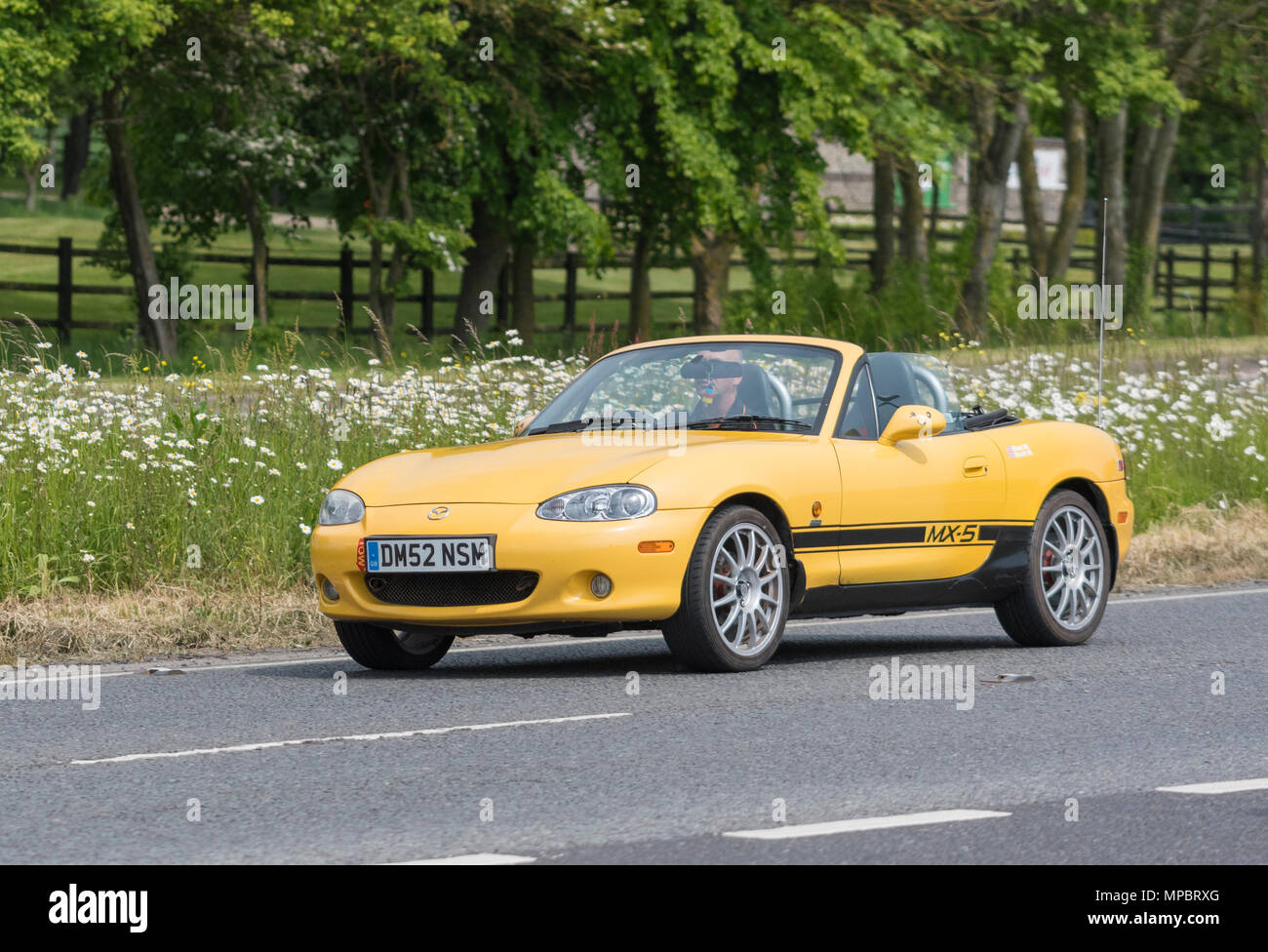 Yellow Mazda MX-5 Arizona convertible sports car from 2002, with the top down on a British road on a hot day in the UK. Mazda soft top car. - Stock Image