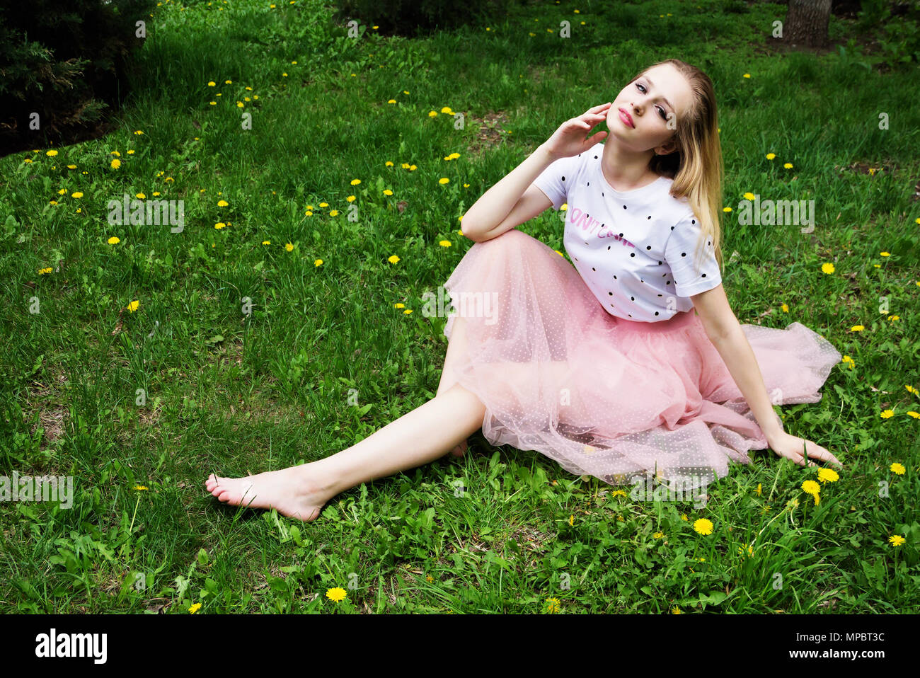 9e2ca9f63db Beautiful barefoot blonde girl with long hair resting on the green grass. -  Stock Image