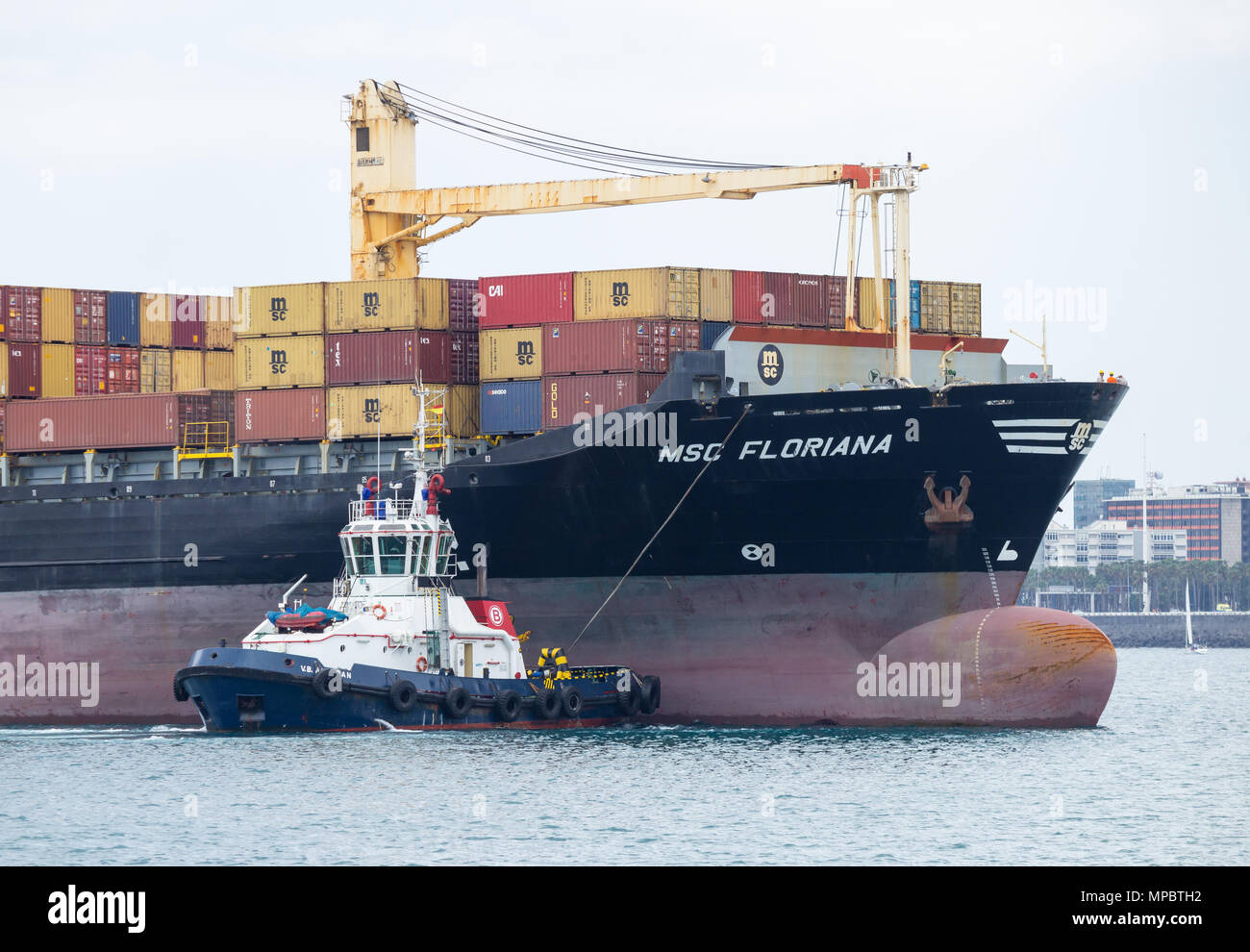 Tug boats guiding MSC Floriana container ship into port in Las Palmas on Gran Canaria, Canary Islands, Spain - Stock Image