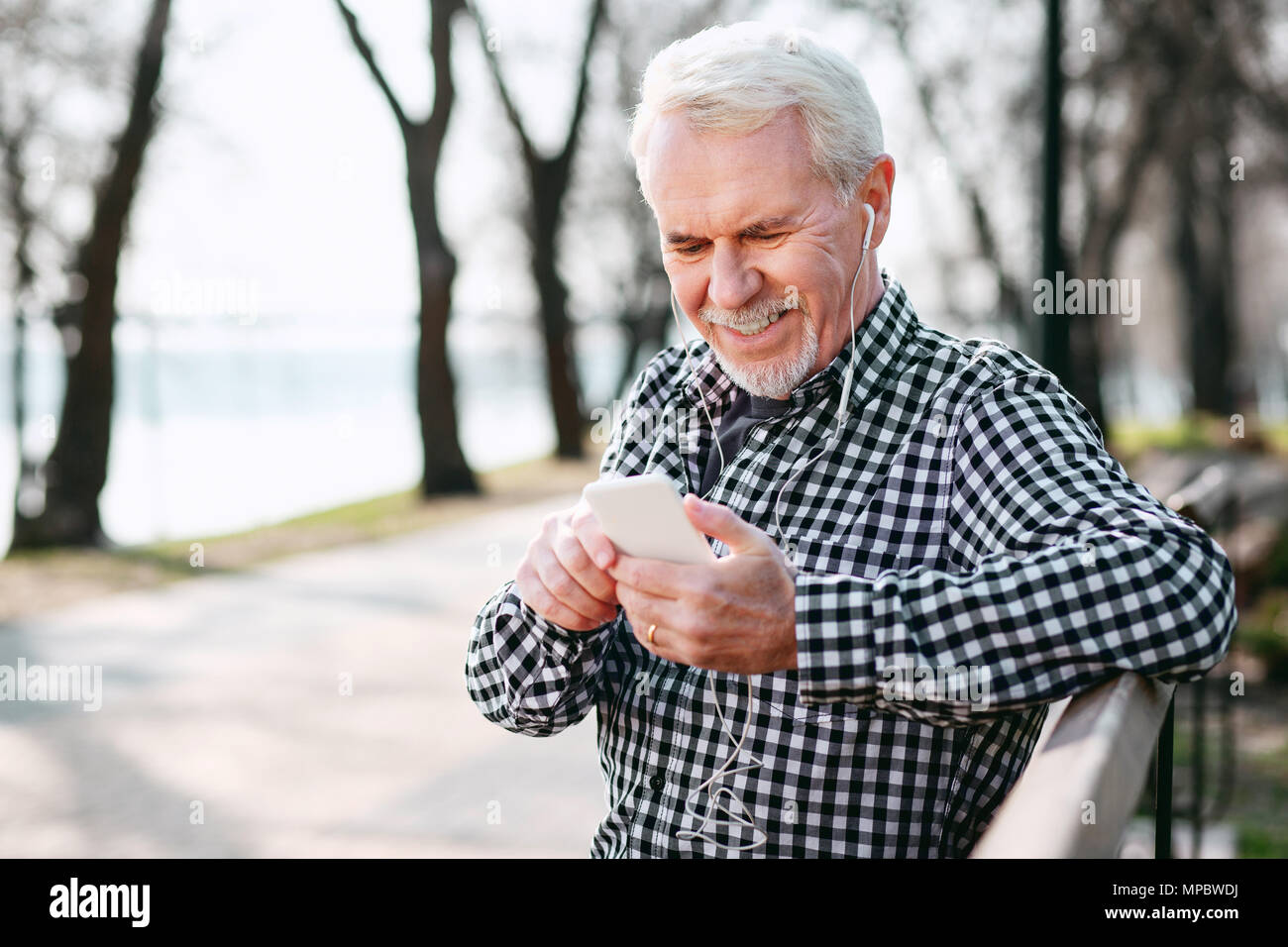 Merry senior man choosing playlist - Stock Image