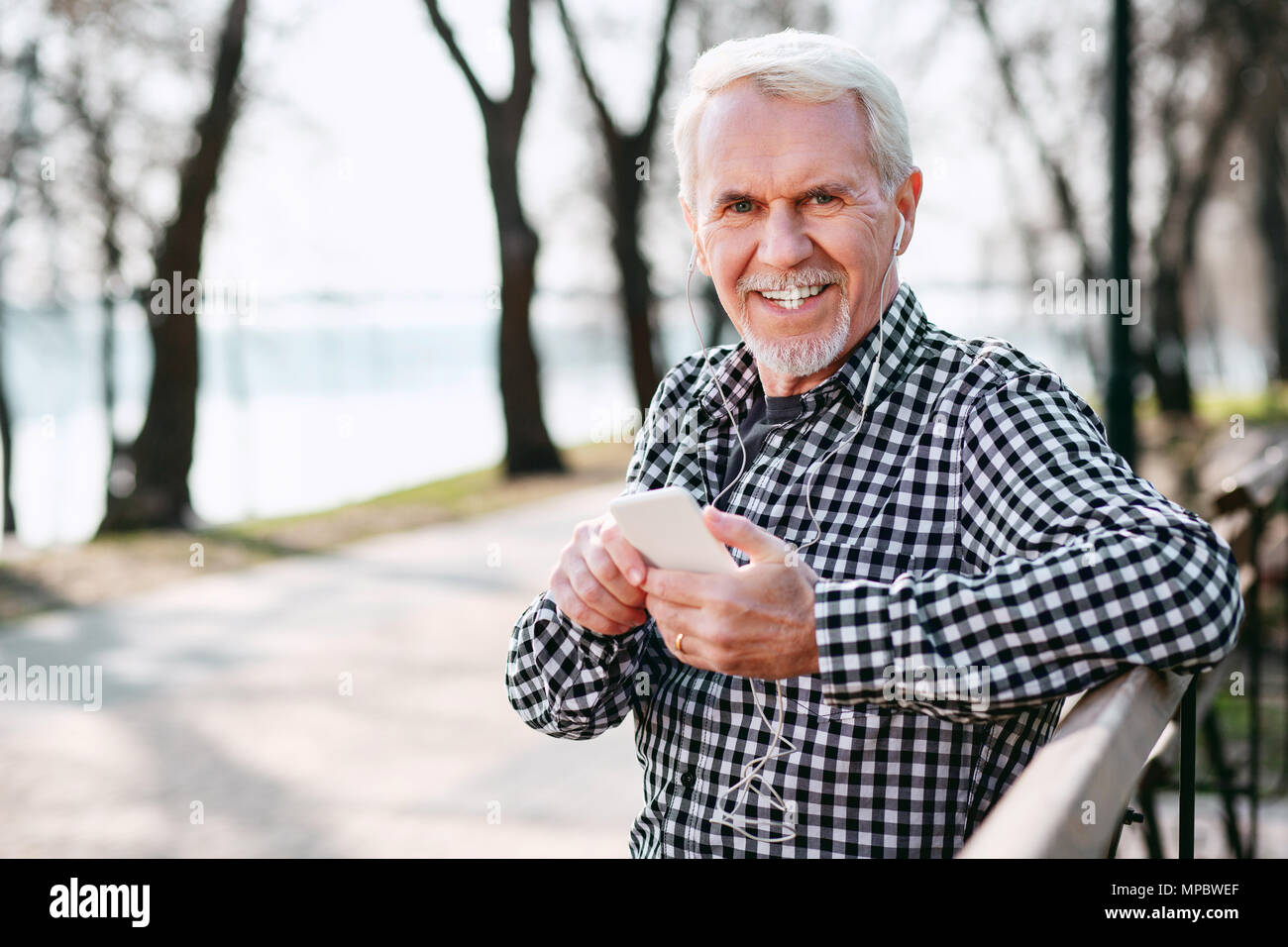 Happy senior man selecting playlist - Stock Image