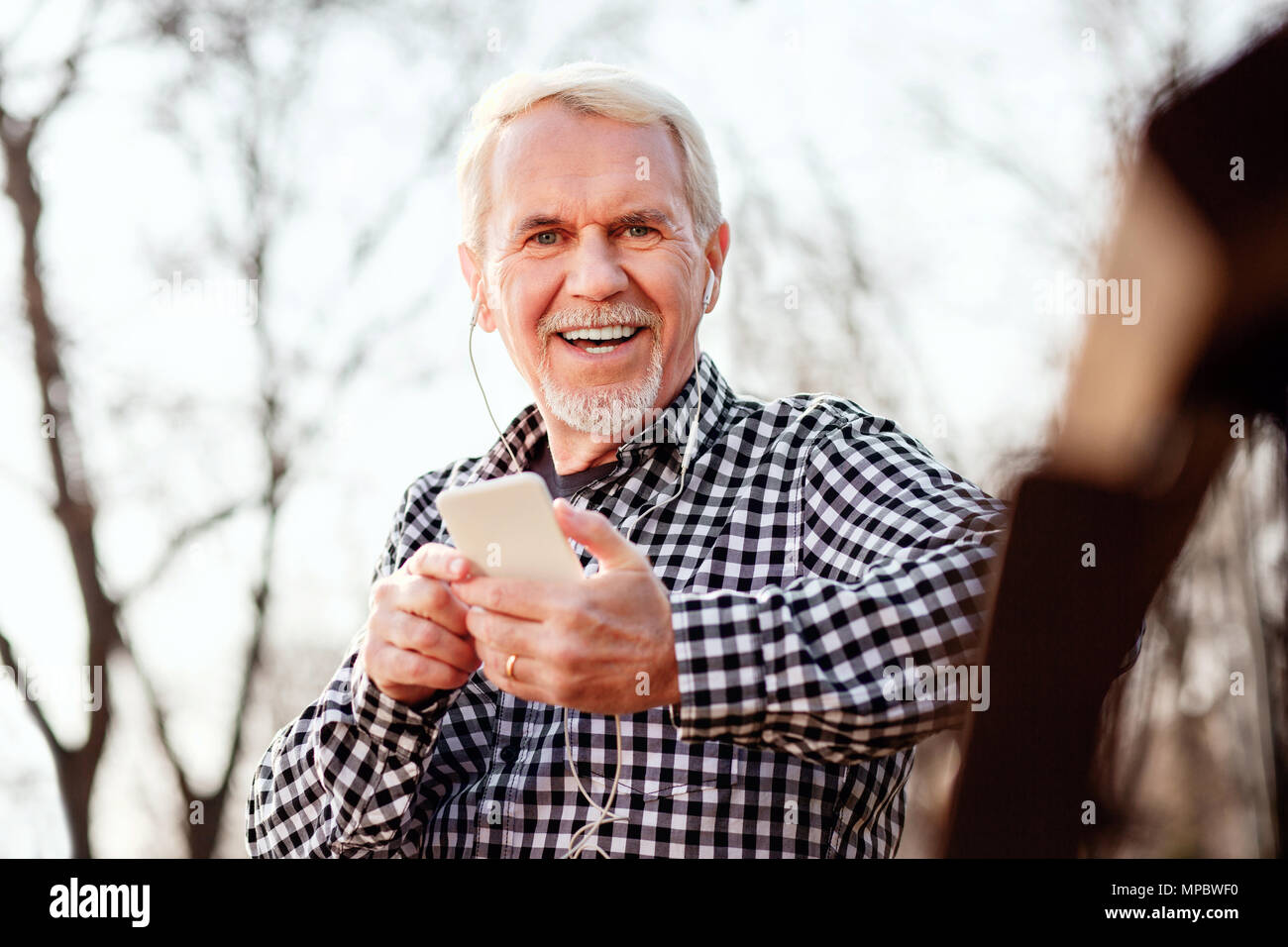 Joyful senior man picking up playlist - Stock Image
