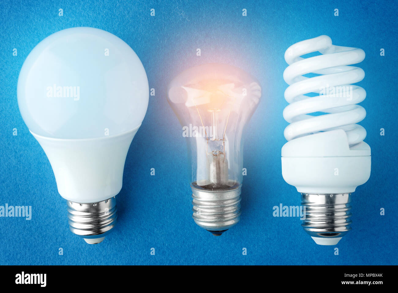 two LED lamps and an incandescent lamp on a blue background. Top view - Stock Image