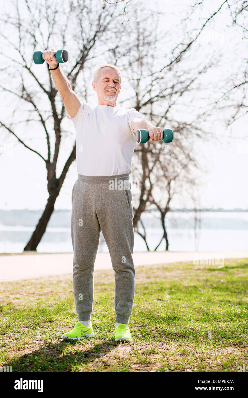 Focused mature man strengthening muscles - Stock Image
