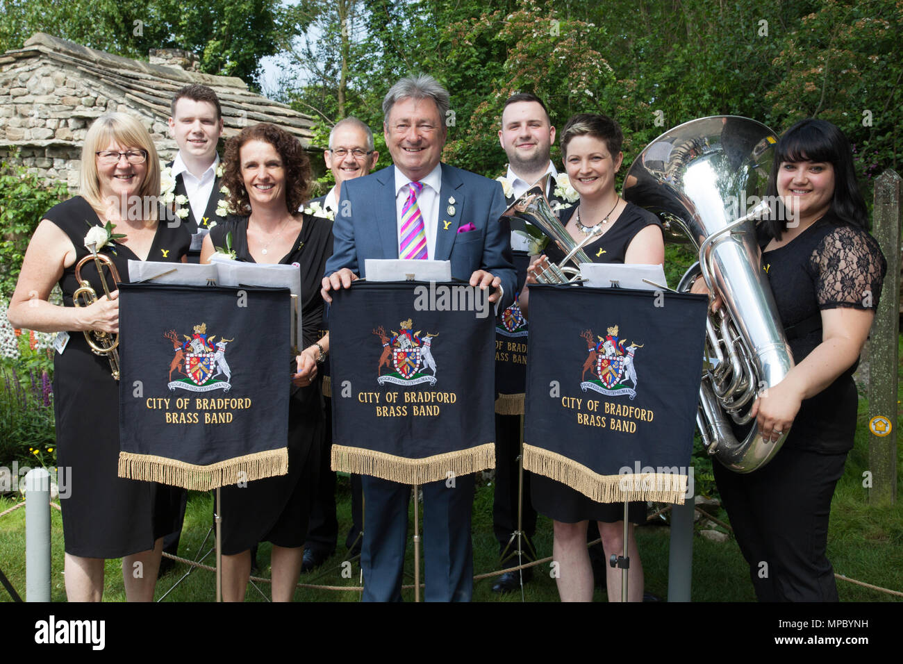 Chelsea, London, UK. 21st May, 2018. Chelsea, London, UK. 21st May 2018. Sir Alan Titchmarsh with the City of Bradford Brass Band on the Welcome to Yorkshire garden at Chelsea Flower Show 2018, designed by Mark Gregory for Landformconsultants.co.uk Credit: Jenny Lilly/Alamy Live News - Stock Image